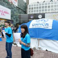 A tent used to provide emergency shelter at U.N. refugee camps is set up in front of Shibuya Station on Saturday to raise awareness of refugee issues ahead of World Refugee Day on June 20. | CHISATO TANAKA