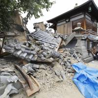 The gate of a temple collapses after an earthquake hit Ibaraki city, Osaka Prefecture, on June 18, 2018. | KYODO