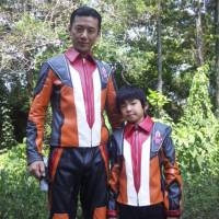 Actor and single father Ryuichi Oura and his son, Sunowa, show off their Ultraman commander suits in Tokyo in July 2014. | COURTESY OF RYUICHI OURA / VIA KYODO