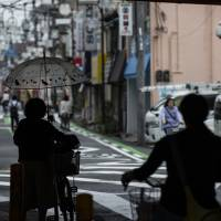 People are seen at a shopping street in Kadoma, Osaka Prefecture, on June 8. A fatal domestic violence case that resulted in the death of 4-year-old boy has cast light on the economic plight of single mothers in Japan. | BLOOMBERG