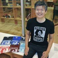 Designer Yasukazu Asano poses with T-shirts he produced with the phrase 'Osako hanpa naitte' ('Osako is way too good') printed on them in May in Tokyo's Chiyoda Ward. | KYODO