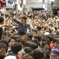 Soccer fans celebrate in Tokyo's Shibuya district Tuesday after Japan defeated Colombia in a World Cup Group H match in Russia. | KYODO