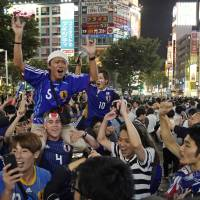 Fans celebrate in Shibuya after Japan beat Colombia in the Group H World Cup soccer match on Tuesday. | AP