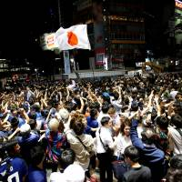 Soccer fans cheer near the scramble crossing in Tokyo's Shibuya district Monday following the Group H World Cup soccer match between Japan and Senegal in Russia. | REUTERS