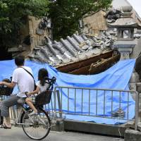 A man and a child on a bike pass the collapsed gate of a temple in Ibaraki, Osaka Prefecture, on Tuesday, a day after a magnitude 6.1 earthquake rocked the Kansai area. | KYODO