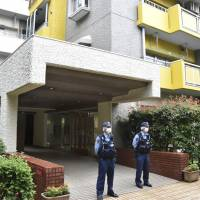 Police officers on Thursday stand in front of a Yokohama apartment building where a man reportedly slashed three people and fled earlier in the day, killing one. | KYODO