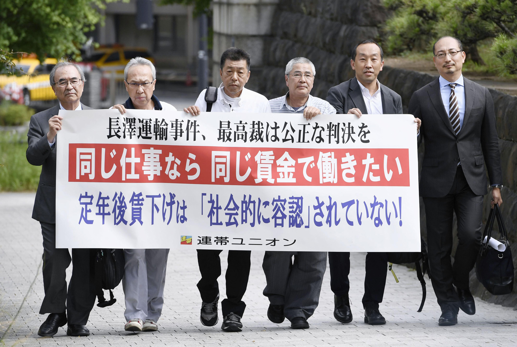 Driven to court: The three truckers in the Nagasawa-Unyu case, flanked by their lawyers, arrive at the Supreme Court on June 1 holding a banner calling for equal pay for equal work. | KYODO