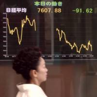 Lost confidence: A woman walks past an electronic stockboard in Tokyo's Yurakucho district that shows the Nikkei index ending trade at 7,607.88 on April 28, 2003. The index had been as high as 21,000 in the mid-1990s. | KYODO