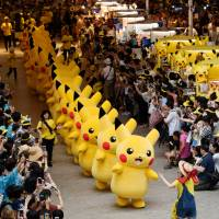 """Performers dressed as the Pikachu character from Nitendo Co.'s """"Pokemon"""" franchise march through a shopping mall at last year's Pikachu Outbreak event. 