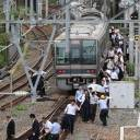 Stranded passengers walk along a railroad track following an earthquake in Osaka on June 18.