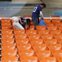 Taking out the trash: Japanese soccer fans collect trash at the end of the match between Japan and Senegal at the 2018 World Cup in Yekaterinburg, Russia, on June 24. | AP