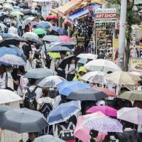 Umbrella-toting shoppers fill a street in the Harajuki area of Tokyo in May. | BLOOMBERG
