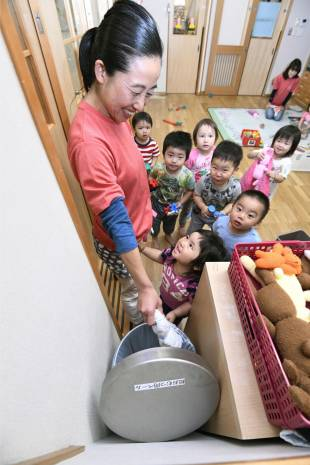 Rubbish problems: A member of staff at a Toshima Ward nursery disposes of a soiled diaper. Japanese children