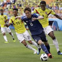 Genki Haraguchi dribbles the ball during Japan's 2-1 win over Colombia on Tuesday at the 2018 World Cup in Saransk, Russia. | AP