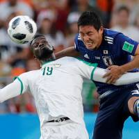 Japan defender Gen Shoji (right) competes with Senegal's M'Baye Niang during their World Cup match on Sunday in Yekaterinburg, Russia. | REUTERS