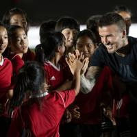 Former England captain David Beckham interacts with children during a promotional event on Wednesday for a sportswear company and a collegiate soccer association in Beijing. | AFP-JIJI