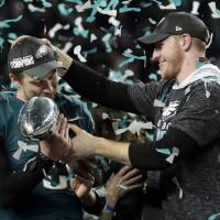 Philadelphia Eagles quarterback Carson Wentz (right) hands the Vincent Lombardi trophy to Nick Foles after winning the NFL Super Bowl 52 football game against the New England Patriots in Minneapolis Feb. 4. The Eagles won 41-33. President Donald Trump has called off a visit by the Philadelphia Eagles to the White House Tuesday due to the dispute over whether NFL players must stand during the playing of the national anthem. Trump says in a statement that some members of the Super Bowl championship team 'disagree with their President because he insists that they proudly stand for the National Anthem, hand on heart.' | AP