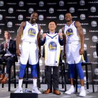 Rakuten, Inc. CEO Hiroshi Mikitani, seen with Golden State Warriors players Draymond Green (left) and Andre Iguodala during a September 2017 news conference, embraces the back-to-back NBA championship team's corporate values and vision. | NOAH GRAHAM / NBAE / GETTY