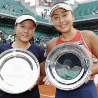 French Open women's doubles runners-up Makoto Ninomiya (left) and Eri Hozumi pose for photos after the final on Sunday in Paris. | KYODO