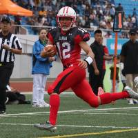 Kyoto University quarterback Daisuke Tanaka carries the ball for Japan during the World University American Football Championship on Saturday in Harbin, China. | KIYOSHI OGAWA