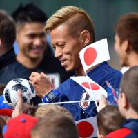 Keisuke Honda signs autographs after a training session on Friday in Kazan, Russia. | AFP-JIJI