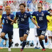 Japan's Yuya Osako (center) celebrates with teammates after scoring the go-ahead goal in the second half against Colombia in their Group H match on Tuesday in Saransk, Russia. Japan won 2-1. | AFP-JIJI