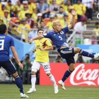 Japan's Keisuke Honda (right) kicks the ball in second-half action against Colombia. | KYODO