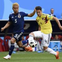 Japan's Yuto Nagatomo (left) and Colombia's Santiago Arias vie for the ball during their Group H match at the 2018 World Cup on Tuesday in Saransk, Russia. | AFP-JIJI