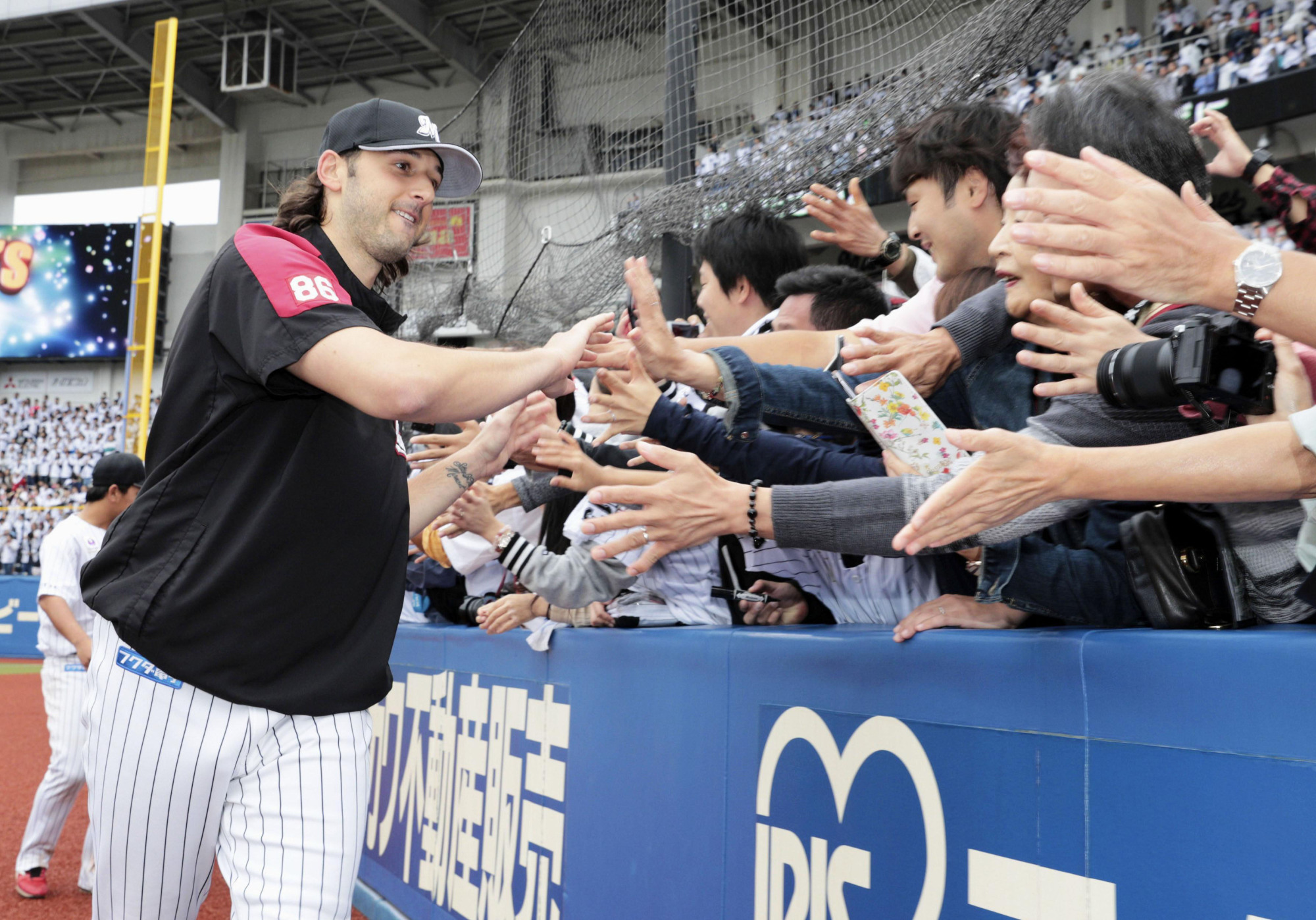 Marines pitcher Mike Bolsinger greets Lotte fans after tossing a shutout on Saturday. | KYODO
