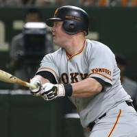 The Giants' Casey McGehee delivers a run-scoring single in the first inning on Friday against the Swallows at Tokyo Dome. McGehee finished with four hits in Yomiuri's 8-5 win over Tokyo Yakult. | KYODO