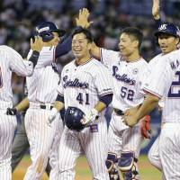 Yuhei Takai (center), who drove in the winning run on a bases-loaded walk, and his Swallows teammates celebrate their 10th-inning victory over the Hawks on Thursday at Jingu Stadium.  Tokyo Yakult triumphed 4-3 over Fukuoka SoftBank.   KYODO