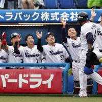 The Swallows' Wladimir Balentien is congratulated by his teammates after hitting a three-run home run against the Buffaloes during the third inning on Sunday at Jingu Stadium. | KYODO