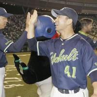 The Swallows' Yuhei Takai (right) and manager Junji Ogawa celebrate after Tokyo Yakult's 6-4 victory over the Seibu Lions on Thursday night. | KYODO