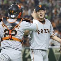 Giants pitcher Shun Yamaguchi (right) celebrates with catcher Seiji Kobayashi after Saturday's 7-1 win over the Swallows at Tokyo Dome. | KYODO