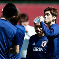 Japan striker Yuya Osako (right) takes a drink during a training session on Friday in Kazan, Russia. | AFP-JIJI