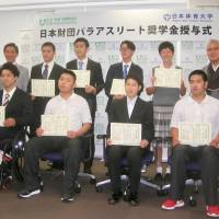 Nippon Foundation chairman Yohei Sasagawa (far left, second row) and eight Paralympic athletes who will receive scholarships from the foundation pose for photos at a ceremony at Nippon Sport Science University in Tokyo on Tuesday. | KAZ NAGATSUKA