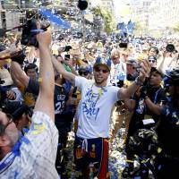 Warriors guard Stephen Curry (center) celebrates with fans during a parade to honor the NBA champions on Tuesday in Oakland, California. | USA TODAY / VIA REUTERS