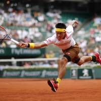 Kei Nishikori reaches for a shot during his French Open fourth-round match against Austria's Dominic Thiem on Sunday. | AP