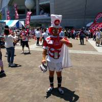 Yoshiharu Okuyama, a 54-year-old fan from Saitama Prefecture, stands outside Noevir Stadium in Kobe before the Japan-Italy game on Saturday. | ANDREW MCKIRDY
