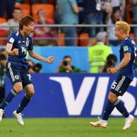 Midfielder Takashi Inui (left) celebrates after scoring a goal during the Russia 2018 World Cup Group H football match between Japan and Senegal at the Ekaterinburg Arena in Ekaterinburg on Monday. | AFP-JIJI