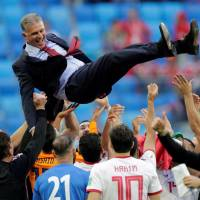 Iran players give Carlos Queiroz a doage as they celebrate their victory over Morocco in the World Cup on Friday night. | REUTERS