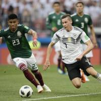 Mexican defender Jesus Gallardo (left) and Germany's forward Julian Draxler compete for the ball during the Russia 2018 World Cup Group F football match between Germany and Mexico at the Luzhniki Stadium in Moscow on Sunday. Mexico won the match 1-0. | JUAN MABROMATA / VIA AFP-JIJI