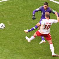 Denmark's Christian Eriksen (right) vies for the ball with Australia goalkeeper Mathew Ryan in the first half of a Group C match at the World Cup on Thursday in Samara, Russia. | AFP-JIJI