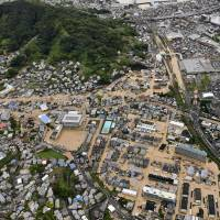 The town of Saka, Hiroshima Prefecture, is flooded in this photo taken from a Kyodo News helicopter Saturday morning. | KYODO