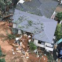Rescuers try to local residents trapped in a mudslide on Saturday morning in Kitakyushu, Fukuoka Prefecture. | KYODO