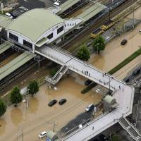 The main road in front of JR Saka Station of Saka, Hiroshima Prefecture, is flooded with muddy water Saturday after heavy rains hit a wide portion of western Japan Friday. NHK reported at least three mudslides were triggered by the heavy rain in the town, leaving two residents missing. | KYODO