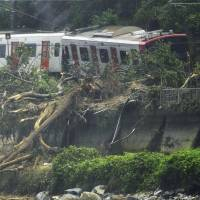 A train sits derailed on a section of the JR Chikuhi Line in Karatsu, Saga Prefecture, Saturday morning after a landslide hit the tracks. | KYODO