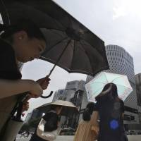 Women shade themselves under parasols in the Ginza shopping district in Tokyo on Monday. In the afternoon the temperature hit 41.1 degrees in Kumagaya, Saitama Prefecture, a new record high for Japan. | AP