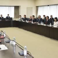 Members of an economy ministry panel discuss how to spread the use of electric vehicles in April. | KYODO