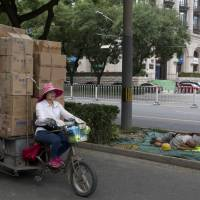 A woman transports goods past workers sleeping on a street-side in Beijing Tuesday. In his trade war with China, U.S. President Donald Trump wields one seeming advantage: The United States could ultimately slap tariffs on more than $500 billion in imported Chinese goods. Beijing has much less to tax: It imported just $130 billion in U.S. goods last year.   AP